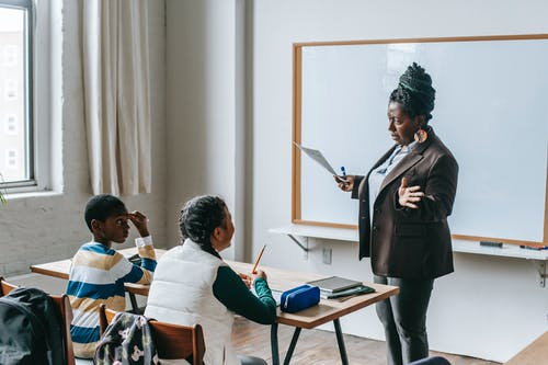 Adult African American female teacher in formal suit standing near whiteboard and explaining new material to multiethnic elementary pupils in light classroom
