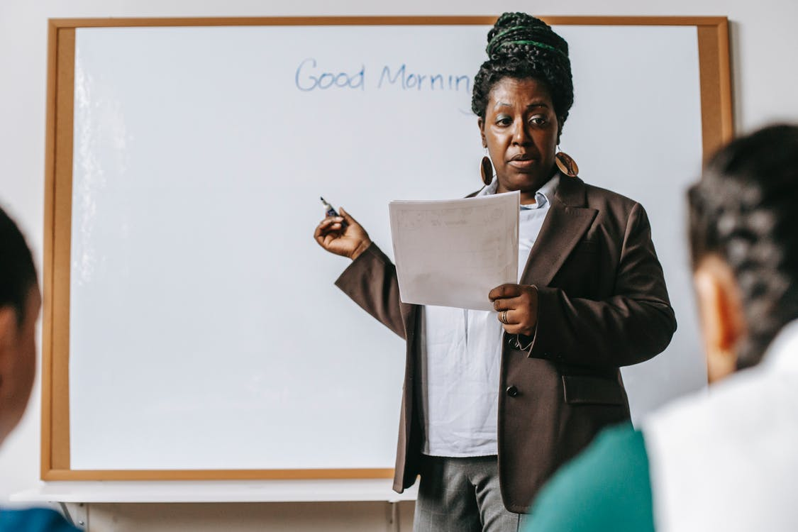 Concentrated adult African American female teacher wearing formal suit standing near whiteboard and talking to pupils in light classroom