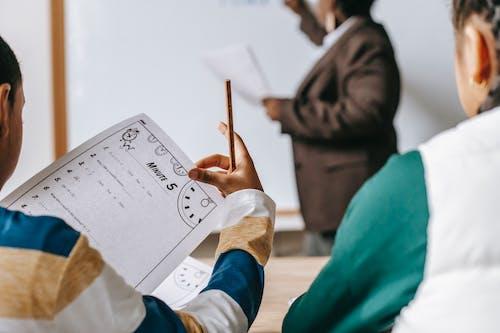 Diverse crop pupils sitting at desk against black teacher