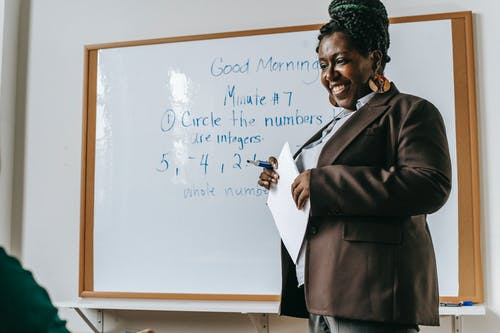 Crop smiling African American female teacher standing near whiteboard with papers in hands during math lesson