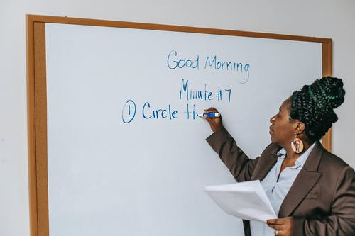 Black female teacher writing on whiteboard