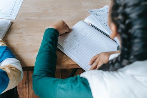 Ritaglia La Studentessa Diligente Senza Volto Seduto Alla Scrivania Con Il Quaderno