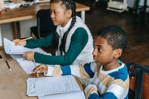 Внимательные одноклассники, сидящие за партой в классе