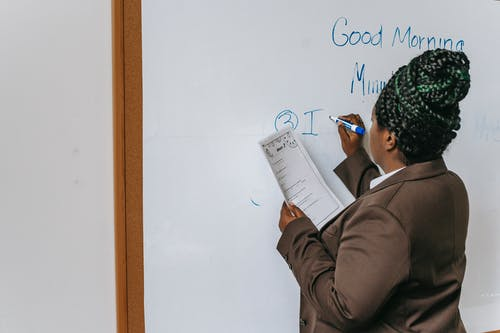 Faceless black female teacher writing on whiteboard