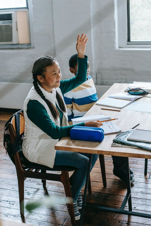 Siswi Asia Yang Ceria Mengangkat Tangan Di Kelas