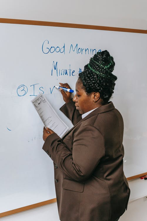 Side view concentrated African American female teacher in formal wear writing plan on whiteboard in auditorium