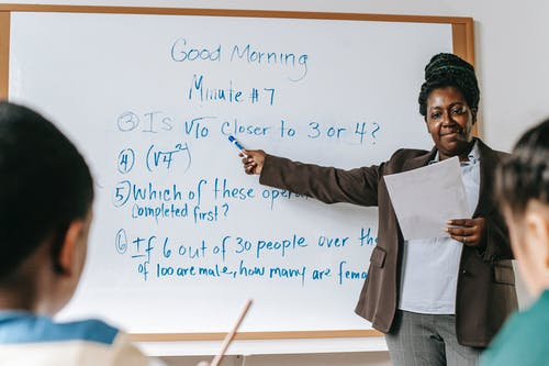 Positive black teacher pointing at tasks on whiteboard