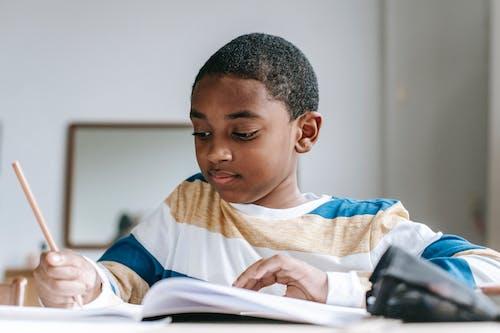 Garoto Negro Positivo Fazendo Lição De Casa No Caderno