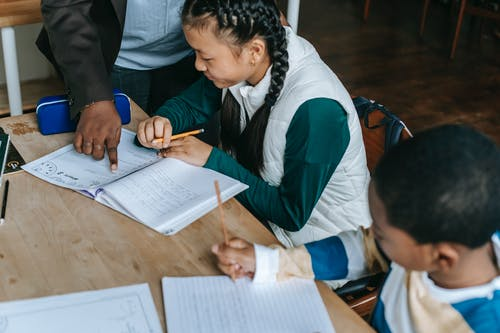 Crop African American teacher standing near desk with diverse classmates and pointing at schoolgirls copybook