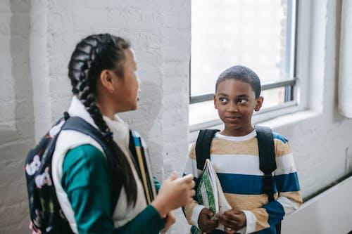 Anak Sekolah Yang Beragam Dan Positif Berdiri Di Koridor Dan Berbicara