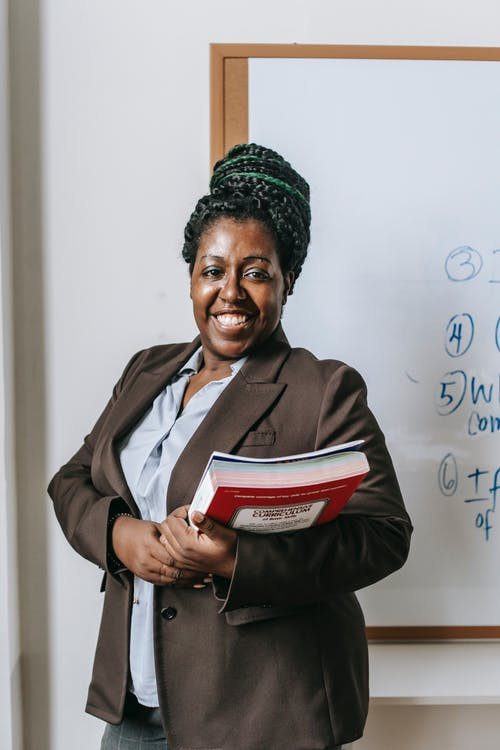 Happy black female teacher  standing with workbooks near whiteboard