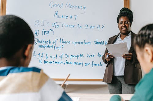 Cheerful African American female math teacher standing near whiteboard and explaining new material to multiracial pupils