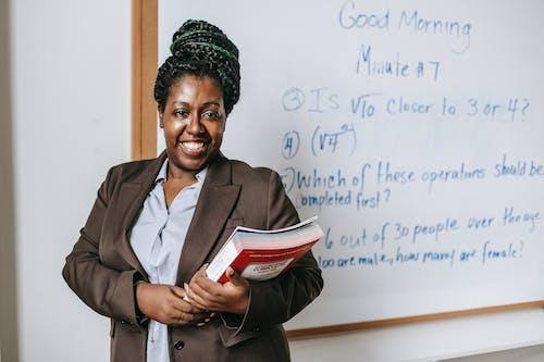 ホワイトボードの近くに立っているワークブックを持つ陽気な黒人女性教師
