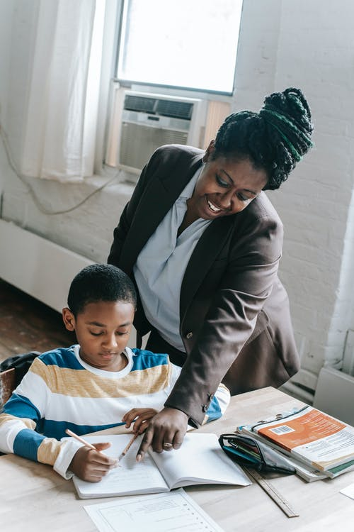 High angle of positive adult African American female teacher in formal clothes helping little boy doing assignment during lesson in school