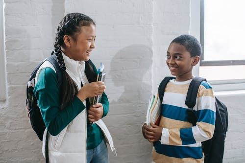 Happy diverse schoolchildren communicating in corridor during break