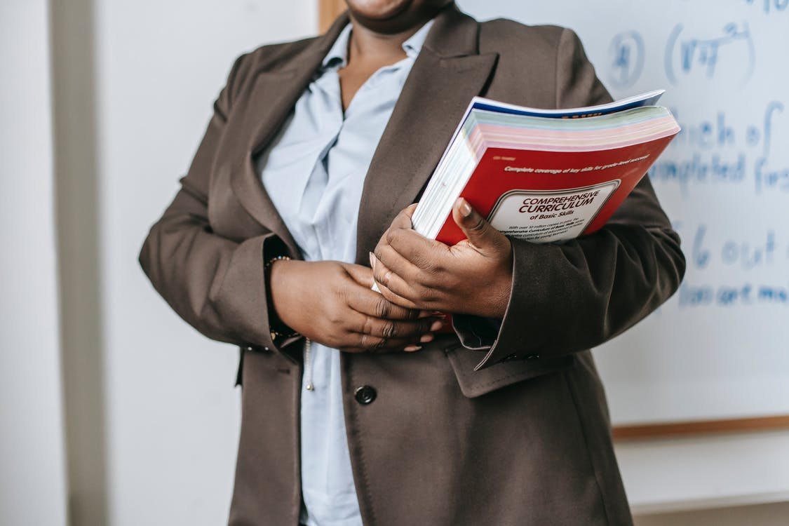 Anonymous black female tutor with books standing near whiteboard at school