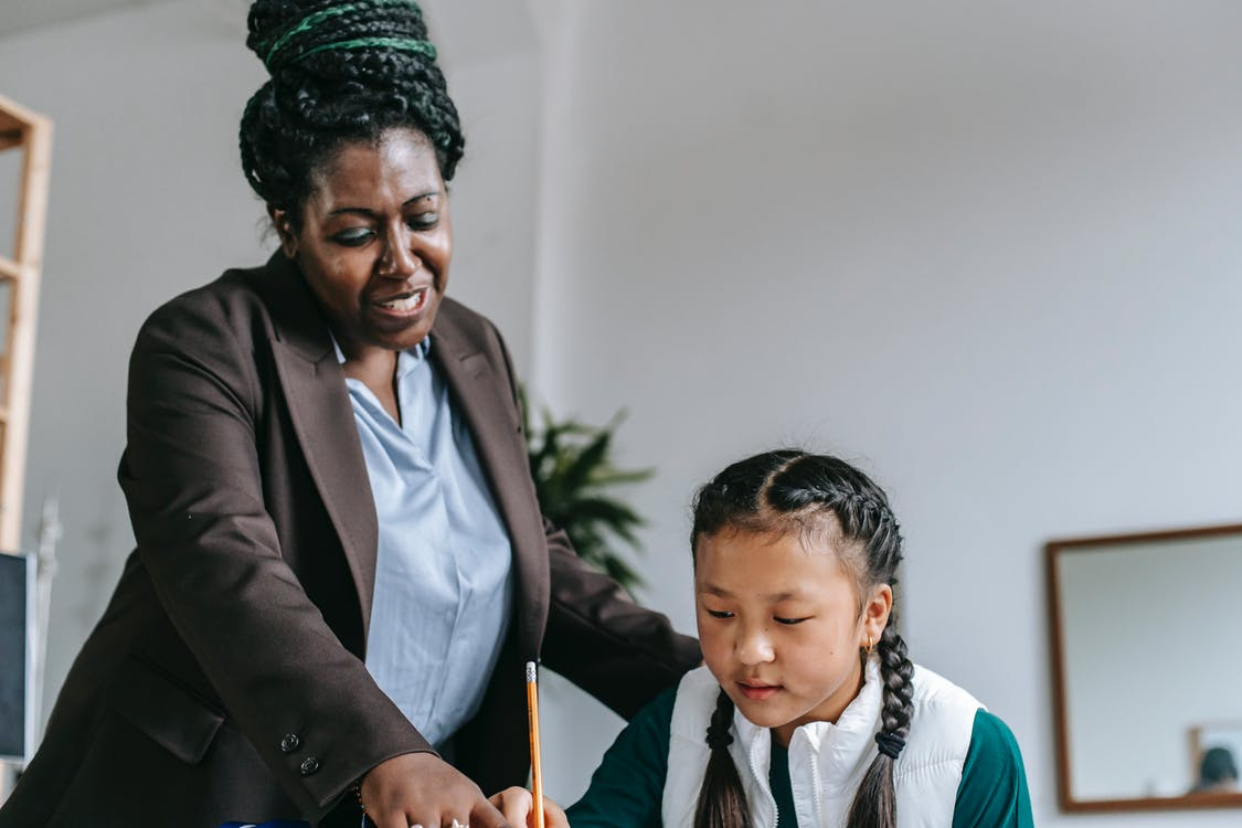 Middle aged African American female teacher with dreadlocks in formal clothes helping smart attentive little Asian girl solving exercise during lesson