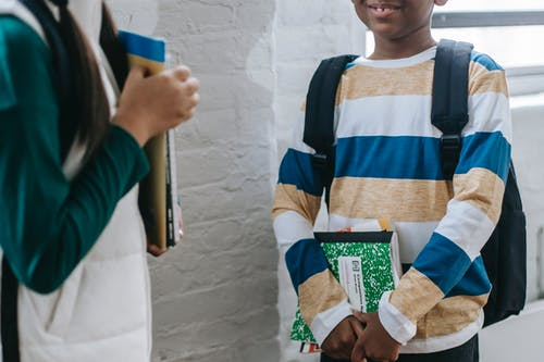 Unrecognizable multiethnic classmates talking in school during break
