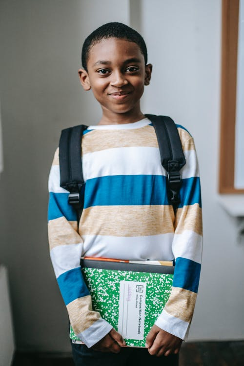 Smiling black child standing in classroom and looking at camera