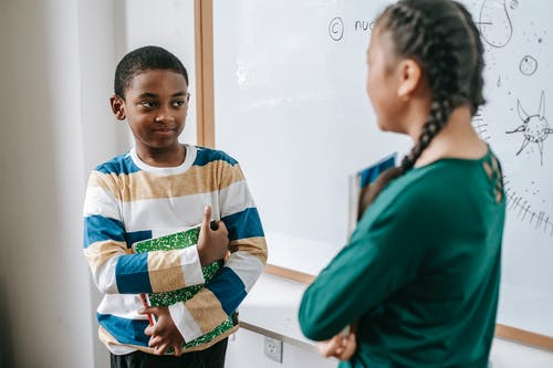 Diverse little classmates speaking near whiteboard during lesson at school