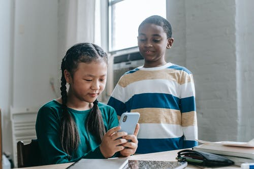 Multiethnic little pupils watching video on smartphone in classroom