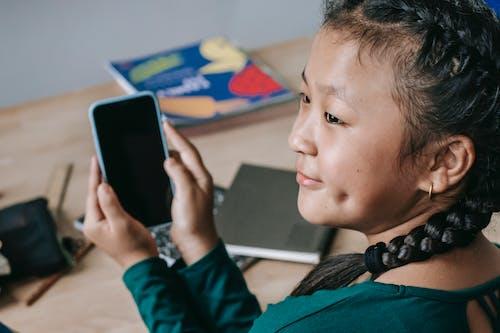 Joyful ethnic child using mobile phone at school