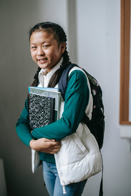 Happy ethnic schoolgirl with stack of textbooks standing in classroom after studies