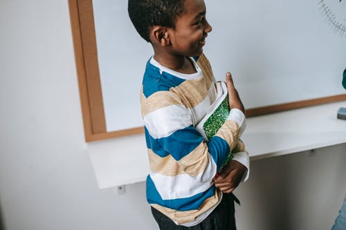 Side view of crop happy little African American schoolboy standing near whiteboard with stack of textbooks and smiling
