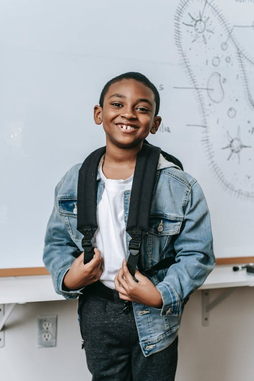 Cheerful black kid standing near whiteboard in classroom