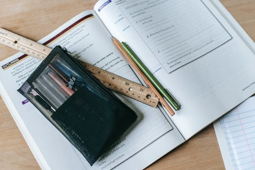 From above of textbook with exercises and ruler with pens near small case on table