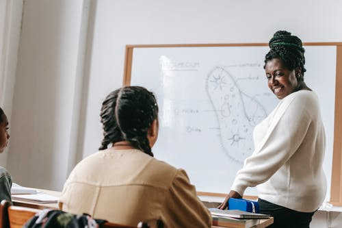 Black woman with students in classroom