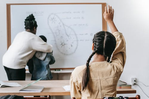 Back view of faceless girl with pigtails sitting at desk and raising hand while teacher  with boy standing near whiteboard and writing