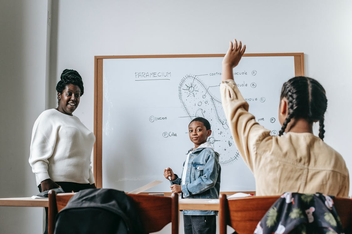 Ethnic girl raising hand while African American female teacher standing near whiteboard with teen boy and explaining task