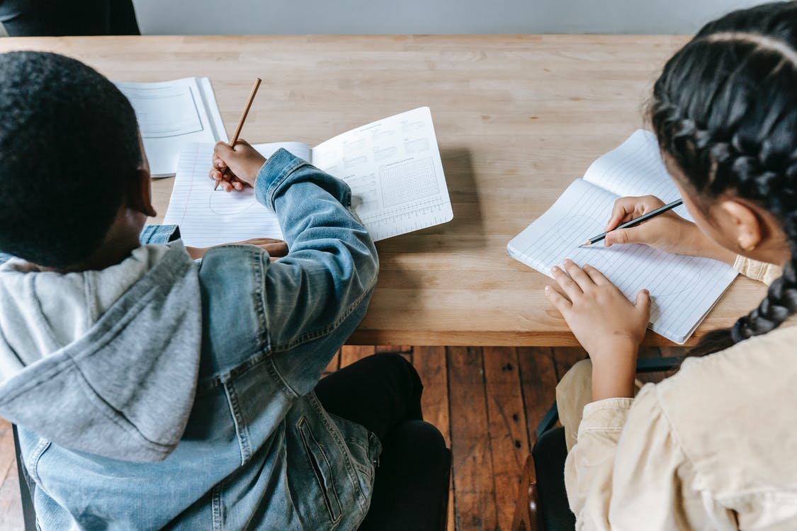 High angle of faceless ethnic schoolchildren in casual clothes sitting at wooden desk with notebooks and pencils while writing task during lesson