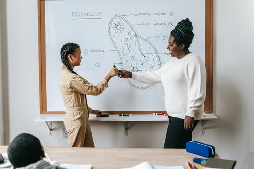 Cheerful woman sharing marker to girl in classroom