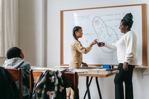 Mujer Negra Dando Marcador A Una Adolescente Asiática