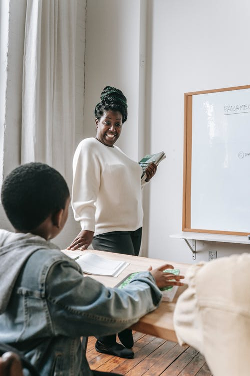 African American female teacher in casual clothes holding books while standing near whiteboard and looking at schoolboy during lesson