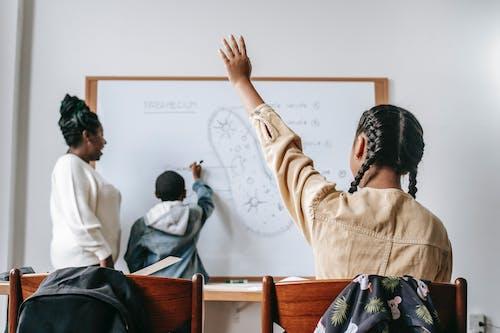 Adolescente Ethnique Levant La Main Pendant La Leçon