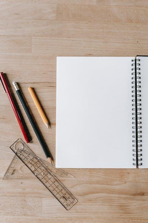 铅笔和尺子在桌上的笔记本附近