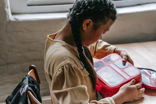 Ethnic teenage with lunch box in school