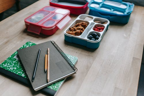 Lunch boxes behind notebooks on table