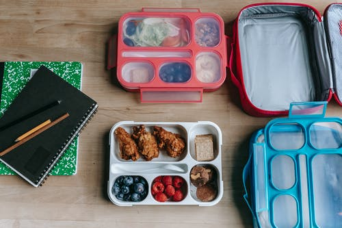 Lunch boxes near notebooks on table