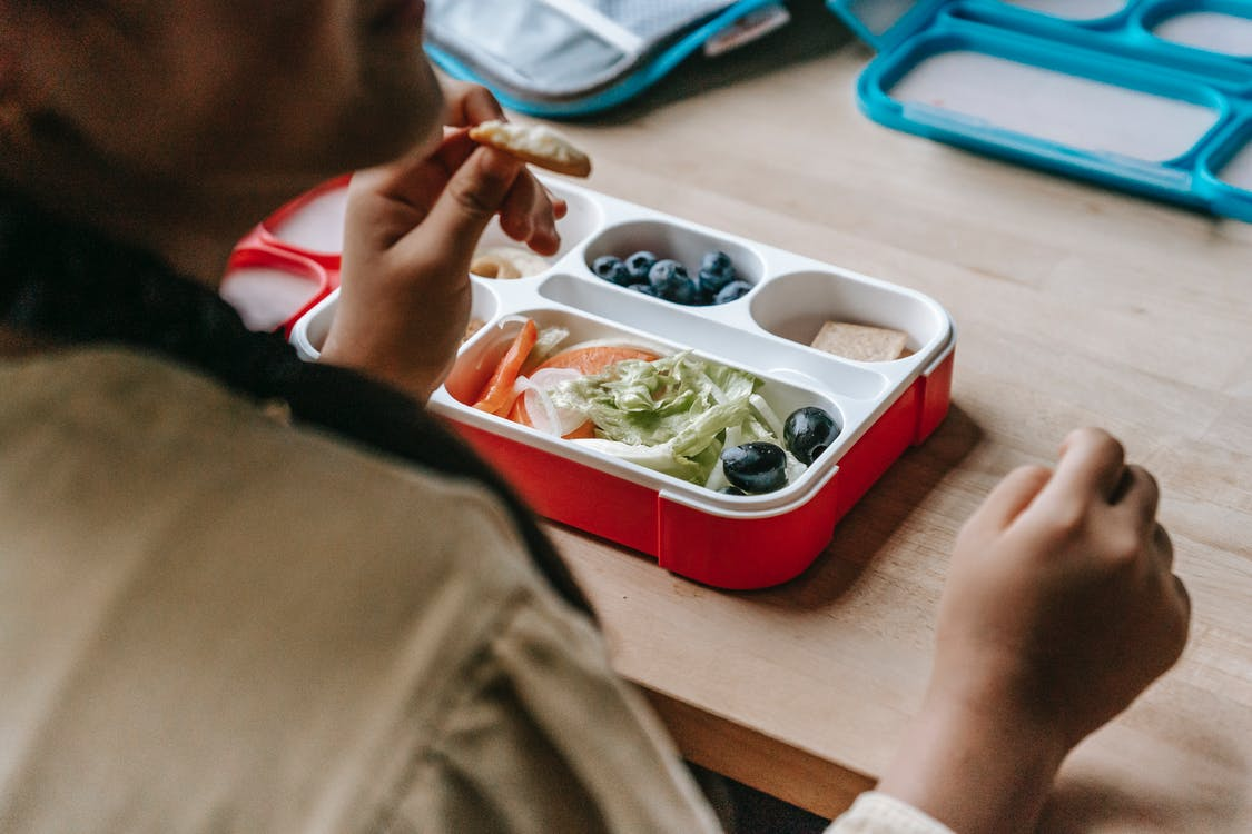 Crop faceless teenage sitting at wooden table with lunch box full of healthy food
