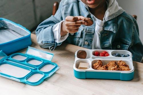 Black boy in denim eating tasty breakfast in plastic container