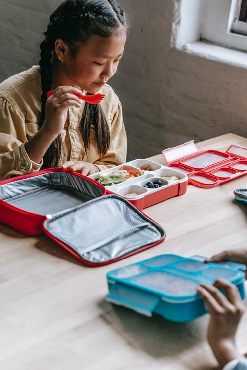 Crop adorable ethnic girl choosing healthy food from plastic container while sitting at table