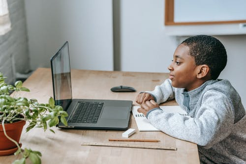 Side view of African American boy watching educational video with netbook while sitting at table with stationery
