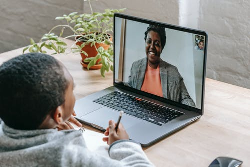 Black boy listening online lesson on laptop
