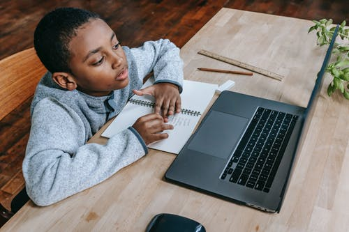 From above of smart cute African American boy studying online with netbook while sitting at table with notebook and pencil