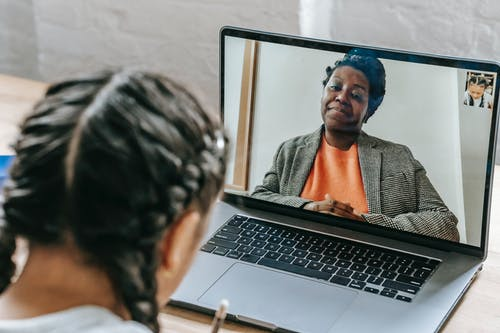 Chica étnica Usando Laptop Mientras Aprende Lecciones En Línea Con El Maestro
