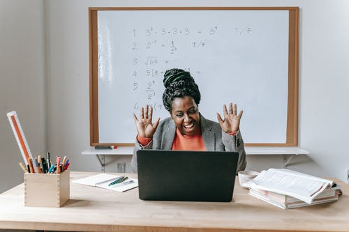使用便携式计算机的愉快的黑人妇女为网上工作